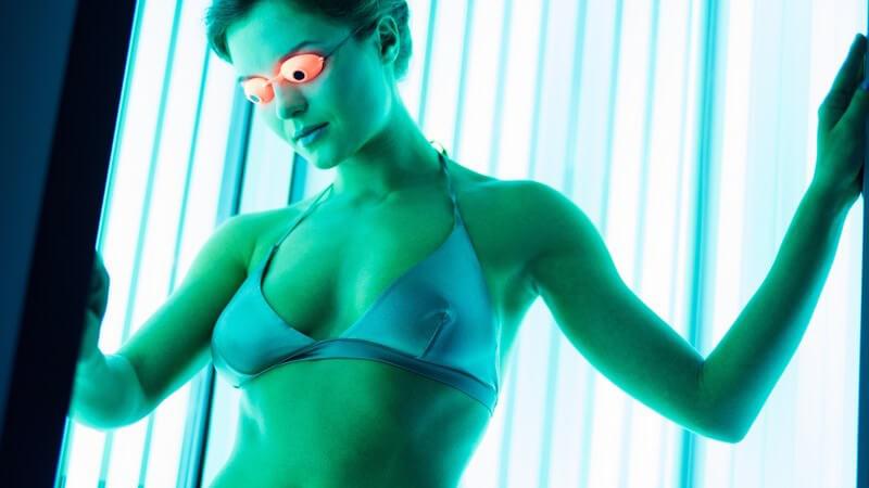Frau in Bikini steht mit Schutzbrille im Solarium