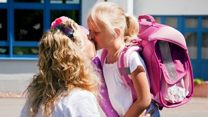 Mutter gibt kleiner Tochter Kuss am ersten Schultag
