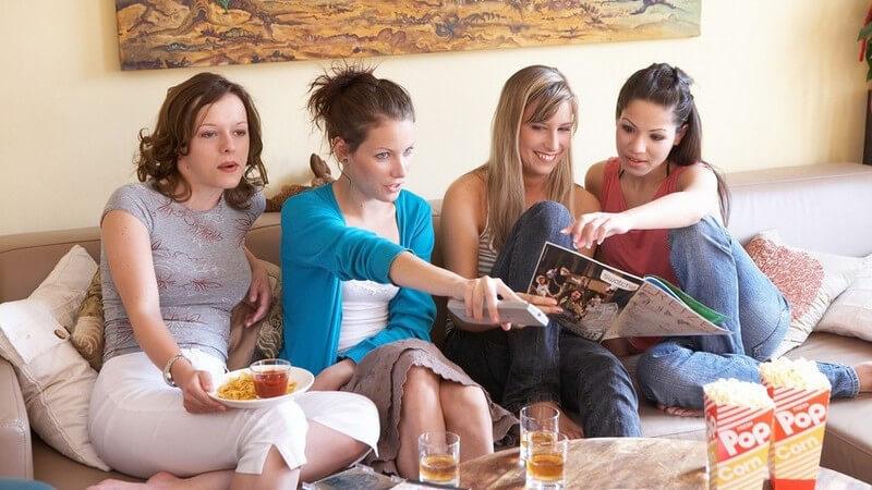 4 junge Frauen auf der Couch mit Popcorn, Getränken, Chips, Zeitschrift und Fernbedienung