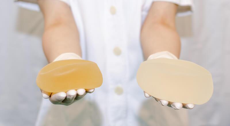 Krankenschwester in weißem Kittel hält zwei unterschiedliche Brustimplantate in den Händen