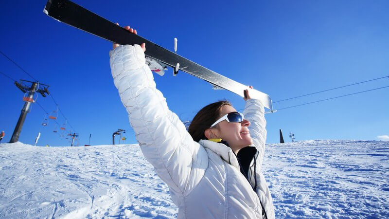 Junge Frau auf Skipiste hält ihren Skier nach oben in den blauen Himmel