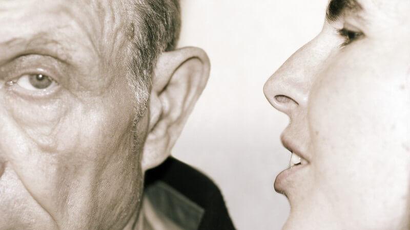 Alter Mann bekommt etwas in sein Ohr gesagt
