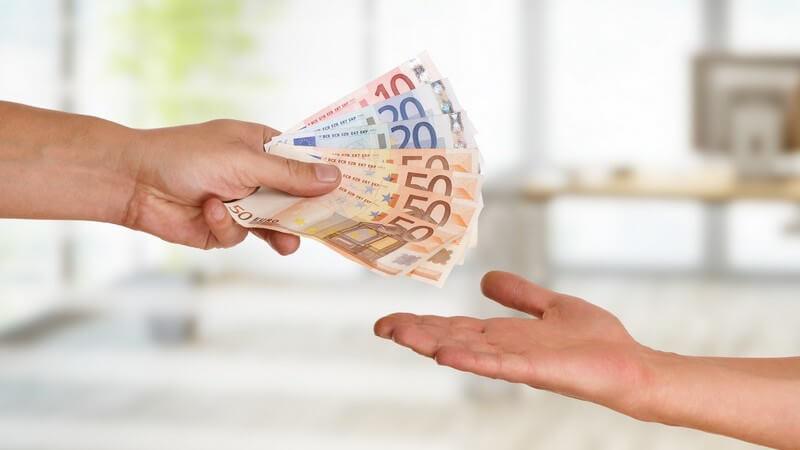 Person überreicht einer anderen handaufhaltenden Person 250 Euro Bargeld