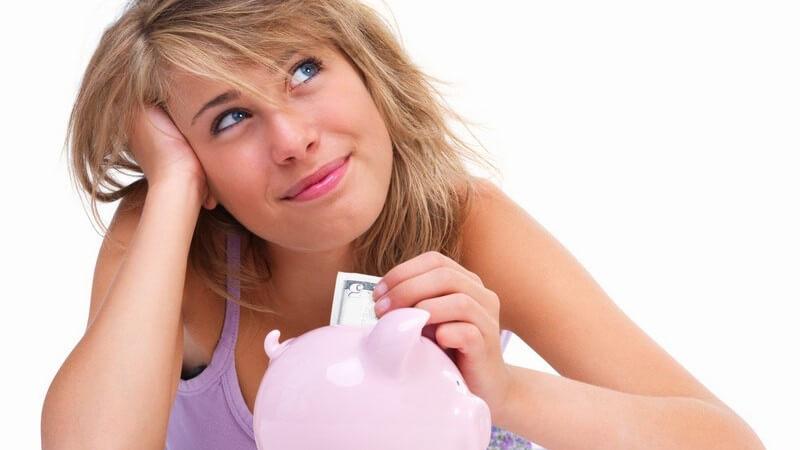 Junge, dunkelblonde Frau liegt auf dem Bauch, stützt Kopf in Hand und steckt Geldschein in Sparschwein