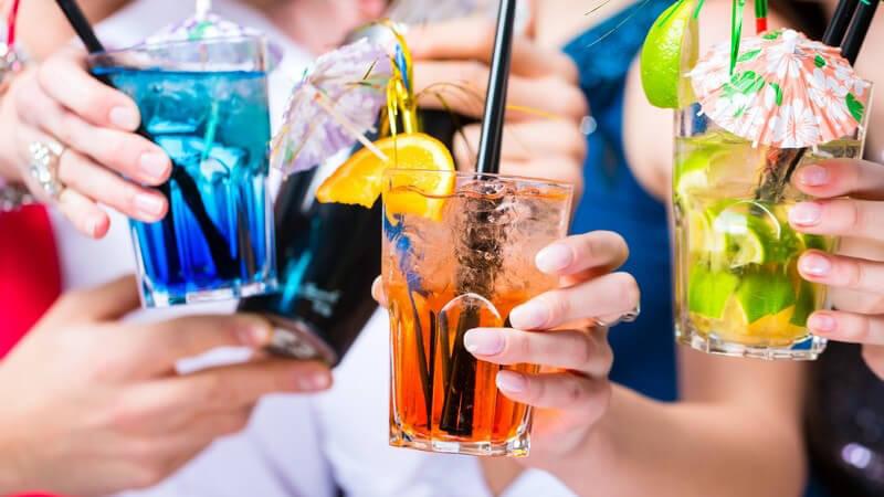 Partygäste mit leuchtend bunten und dekorierten Cocktails in der Hand