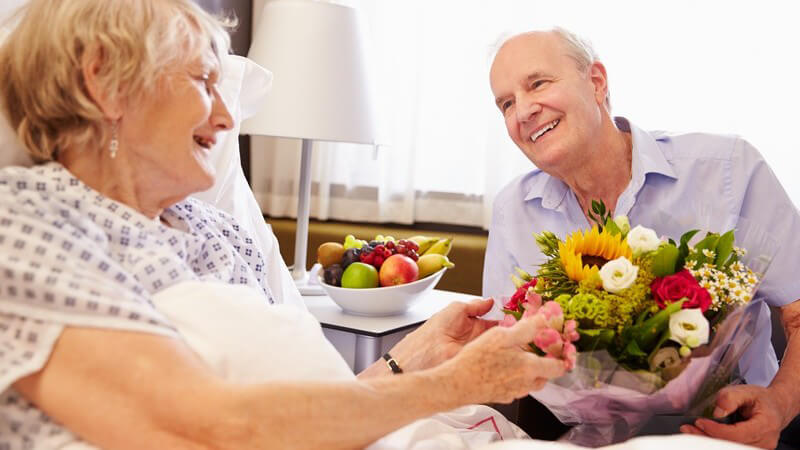 Seniorenpaar im Krankenhauszimmer, er besucht seine Frau am Krankenbett mit Blumen