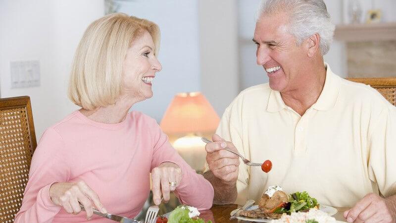 Älteres Paar beim Essen, schauen sich lachend in die Augen