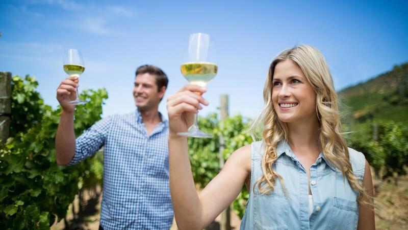 Mann und Frau gehen durch einen Weinberg und halten beide ein Glas Weißwein in die Sonne