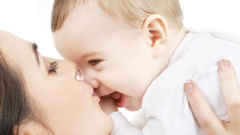 Junge Mutter hebt lachendes Baby hoch und küsst es auf die Nase