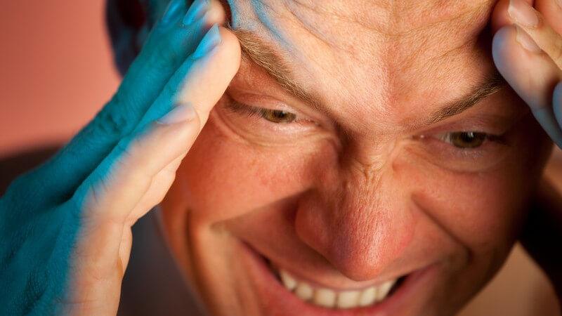 Älterer Mann mit schmerzverzerrtem Gesicht runzelt die Stirn und fasst sich an die Schläfen