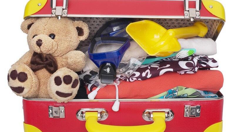 Gepackter Reisekoffer eines Kindes mit Teddybär, Strandspielzeug etc.