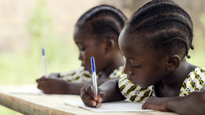 Zwei afrikanische Mädchen sitzen an einem Tisch in der Schule und Schreiben mit einem Kugelschreiber