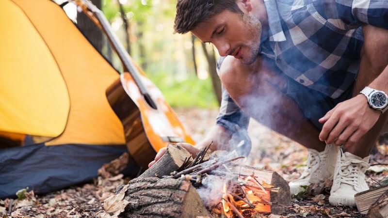Junger Mann in Karohemd entzündet ein kleines Lagerfeuer neben einem Zelt im Wald