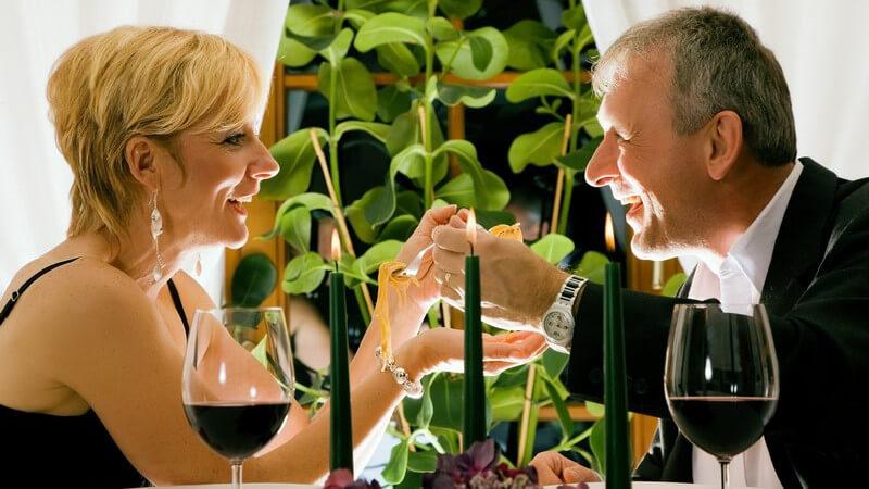 Paar beim Abendessen in Restaurant mit Kerzen, Rotwein