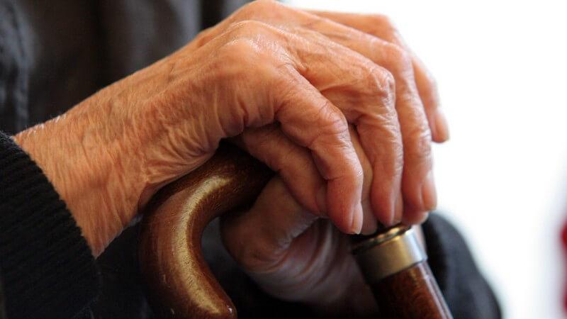 Faltige Hände eines alten Menschen o Seniors mit schwarzer Bekleidung an Gehstock o Krückstock