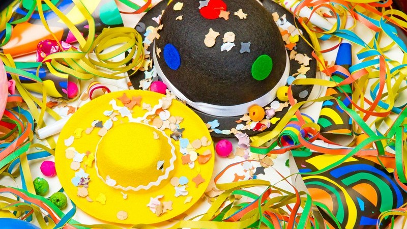 Zwei Partyhüte umgeben von bunten Luftschlangen, Konfetti und Tröten