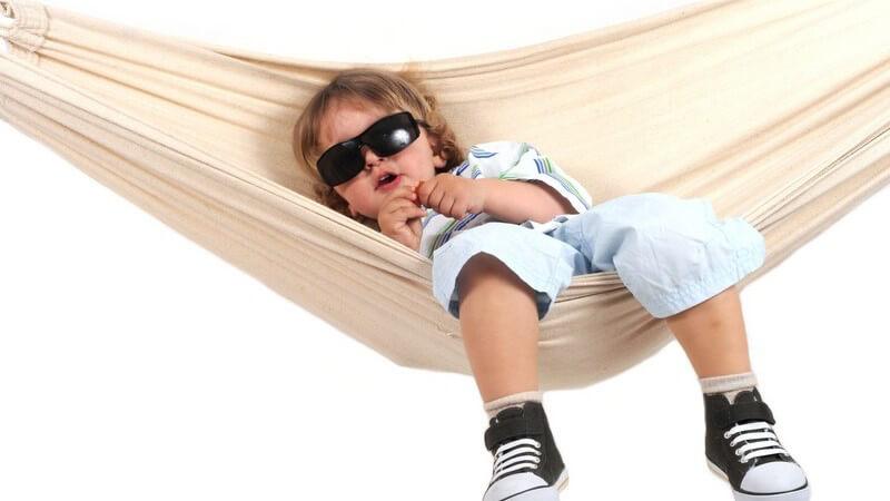 Kleinkind mit Sonnenbrille sitzt in Hängematte