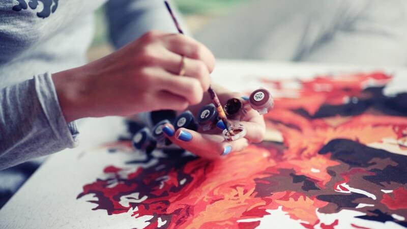 Frau malt ein Bild auf Leinwand, mit Farbpinsel und roten und braunen Farben