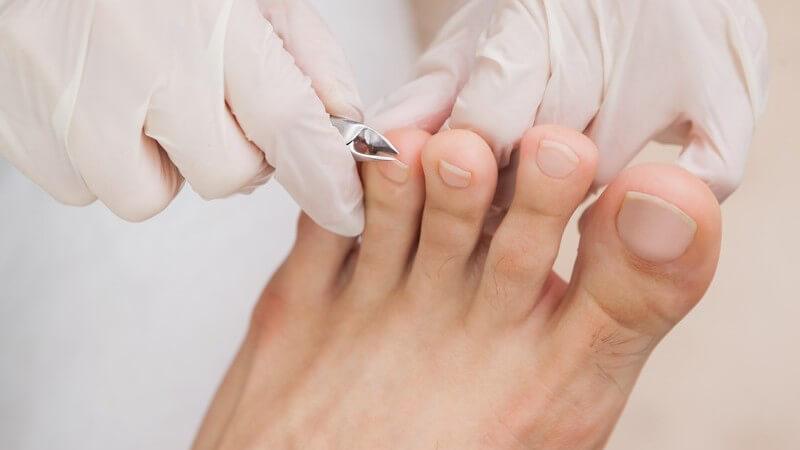 Kunde beim Fußpfleger bekommt die Fußnägel abgeknipst