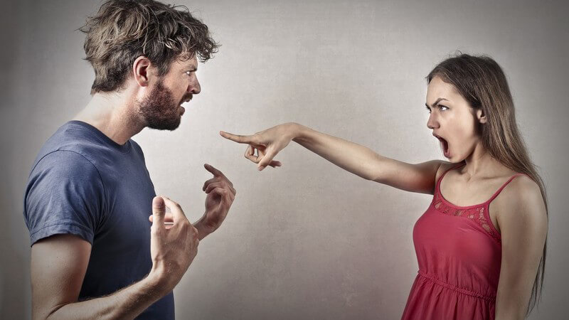Junge Frau in rotem Kleid beschuldigt und zeigt auf ihren Freund in blauem Shirt