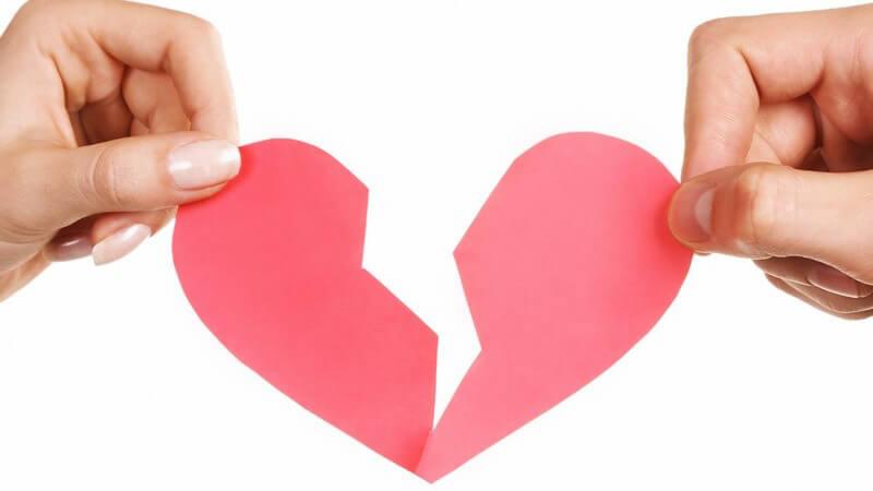 Zerbrochenes Herz aus Papier wird von Frauen- und Männerhand gehalten