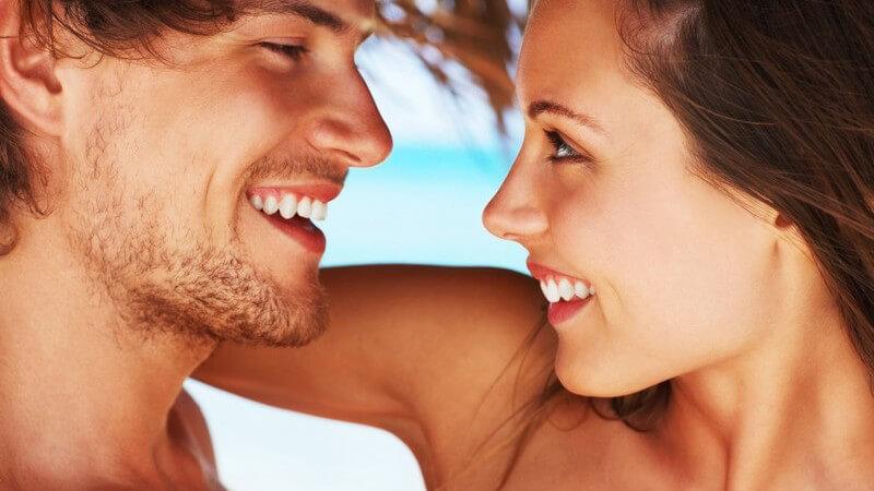 Junges Paar am Strand, beide lachen, schauen sich in die Augen