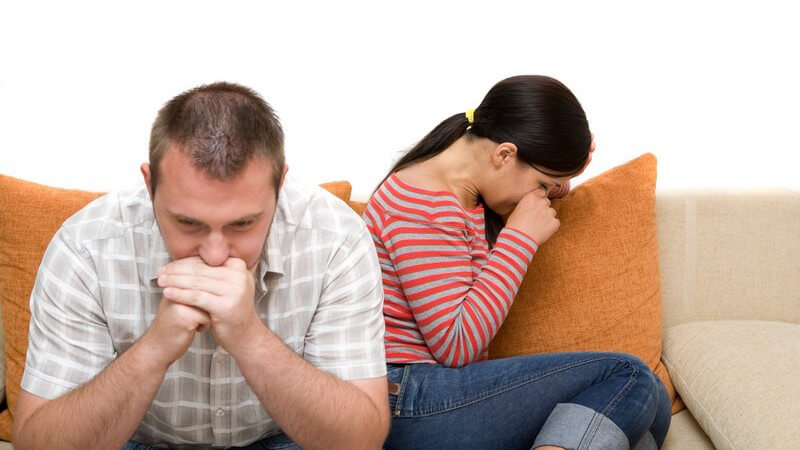 Junges Paar auf Couch, er sitzt vorne nachdenklich, sie von ihm abgewandt weint