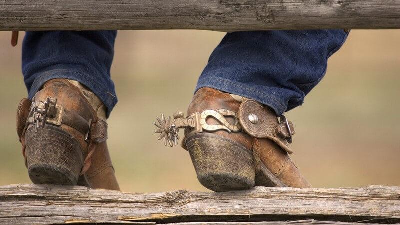 Cowboystiefel an Holzbalken gelehnt, Mann sitzt auf Holzzaun
