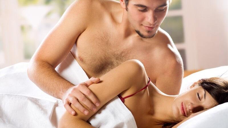 Junges Paar im Bett, sie schläft, er sitzt und schaut sie glücklich an