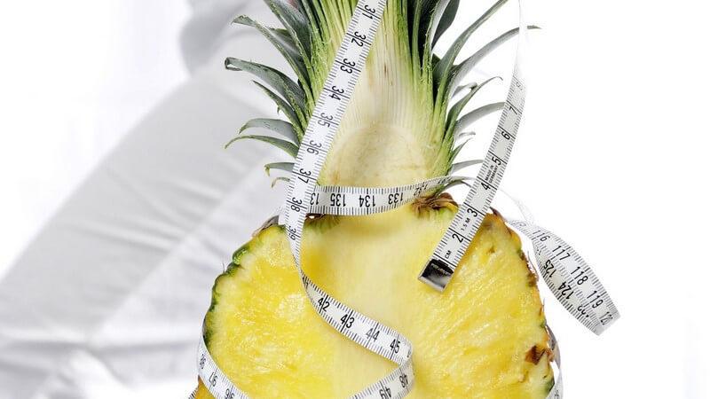Abnehmen - Halbierte Ananas umwickelt mit einem Maßband