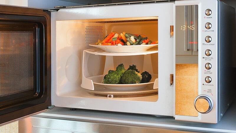 Zwei Teller mit Gemüse stehen in der Mikrowelle