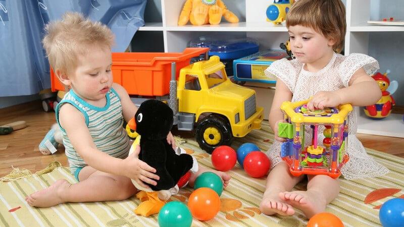 Zwei Kleinkinder mit Spielzeug im Spielzimmer