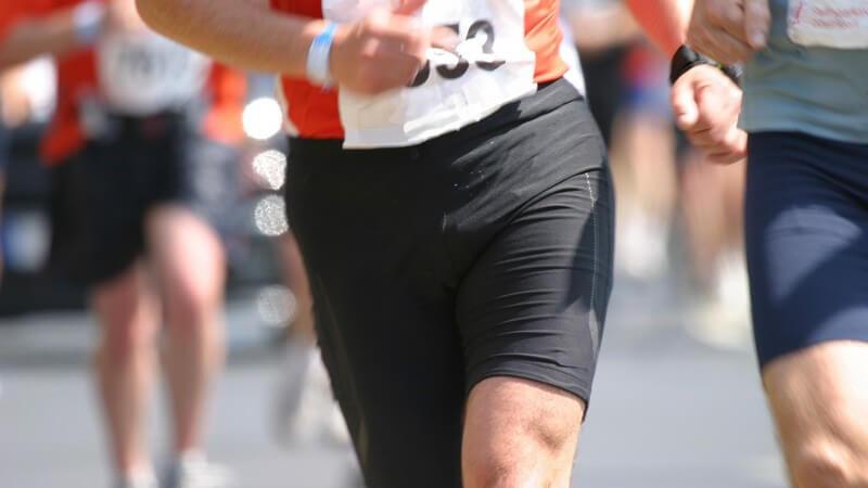 Unterleibe, Beine und Startnummern von Marathonläufern auf der Straße bei Sonne