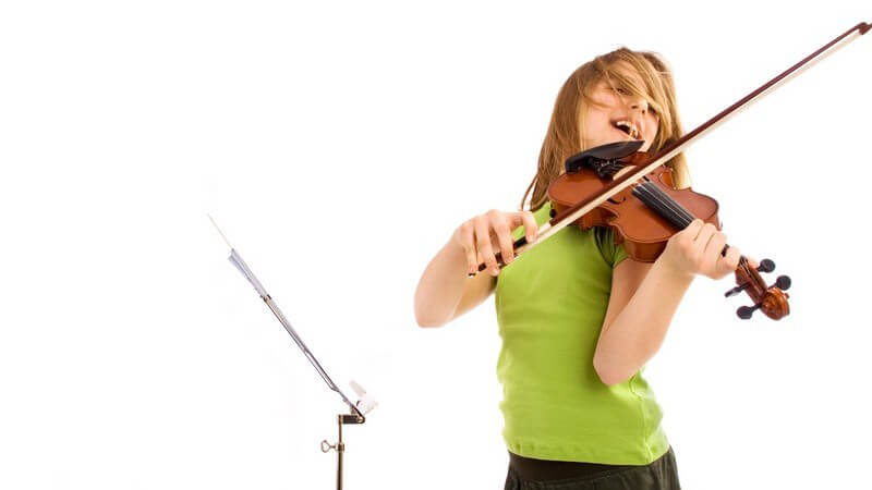 Junges Mädchen steht vor Notenständer und spielt energisch auf der Geige