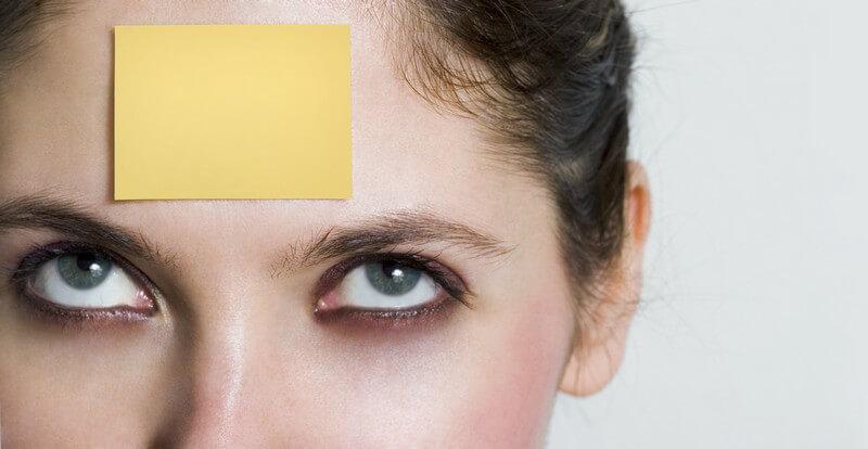 Frau mit gelber Haftnotiz an der Stirn