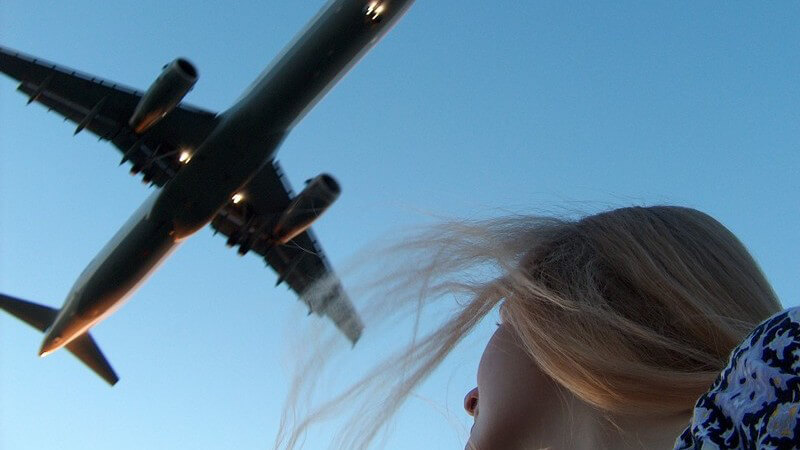 Aufnahme von unten: Frau schaut auf Flugzeug in blauen Himmel