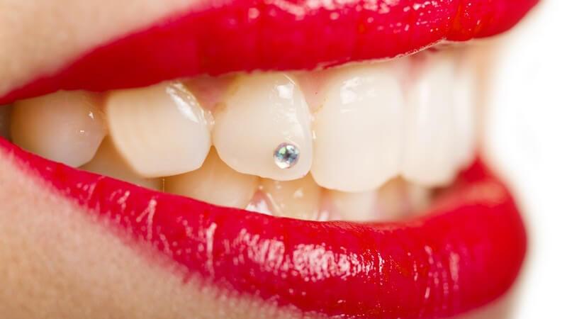 Mund mit rot geschminkten Lippen und einem kleinen Steinchen (Twinkle) als Zahnschmuck
