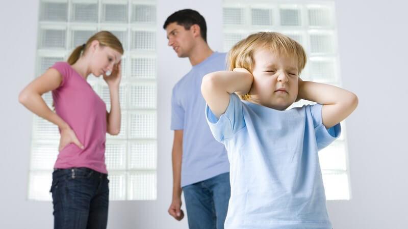 Kleiner Junge mit geschlossenen Augen hält sich die Ohren zu, dahinter junge Eltern beim Streit