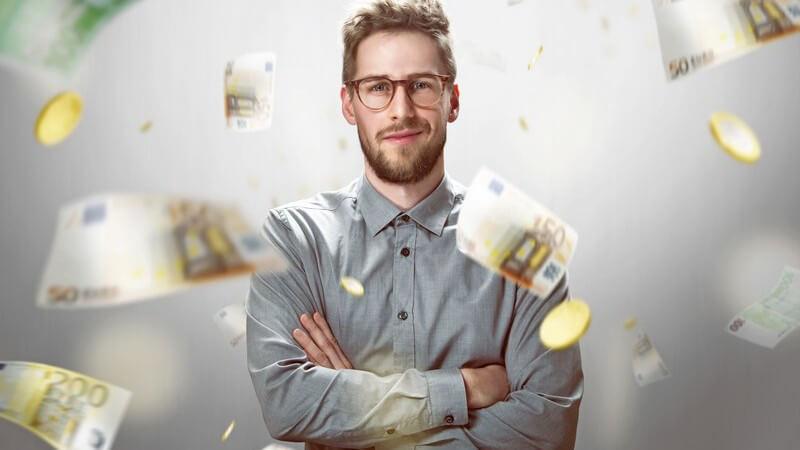 Junger Mann mit Brille und grauem Hemd posiert vor herunterregnenden Euro-Geldscheinen und -Münzen