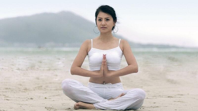Schwarzhaarige Frau in Yogapose im Schneidersitz mit weißem Outfit am Strand
