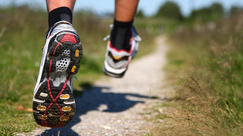 Joggen - Männerfüße beim Laufen, Laufschuhe auf Feldweg