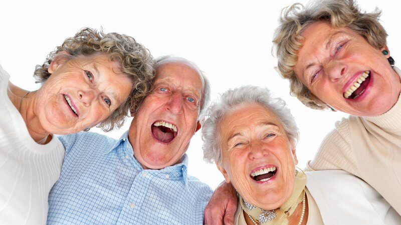 Gruppe alter Menschen lacht in Kamera, weißer Hintergrund