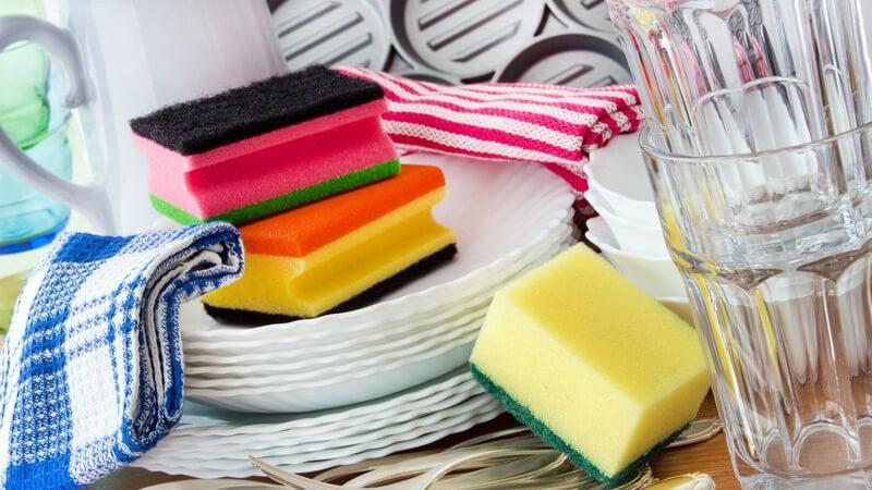 Abwasch in der Küche - gestapeltes Geschirr, Schwämme und Handtücher