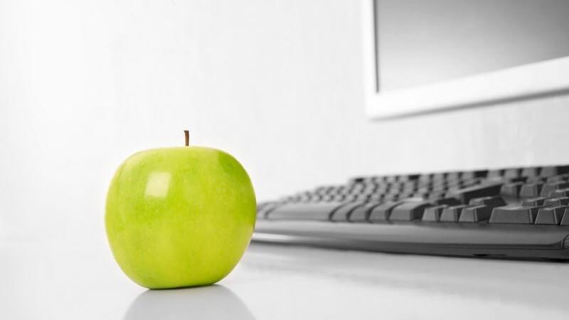 Grüner Apfel auf Tisch vor Computertastatur