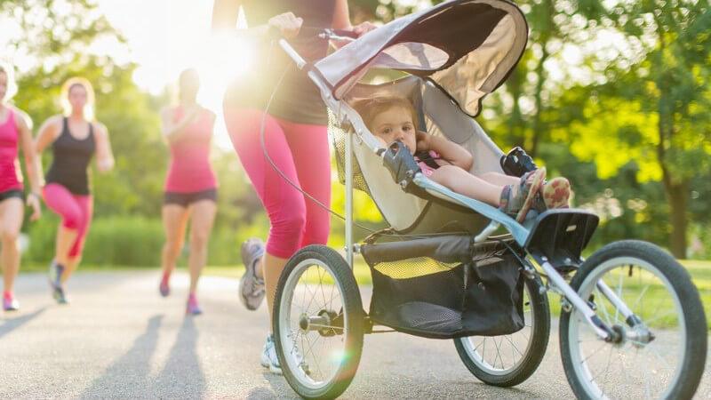 Joggen mit Baby - Frau beim Laufen schiebt Kleinkind im Sport-Buggy