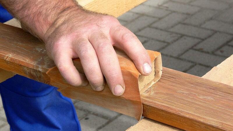 Handwerker oder Schreiner beim Abschmirgeln von Holz
