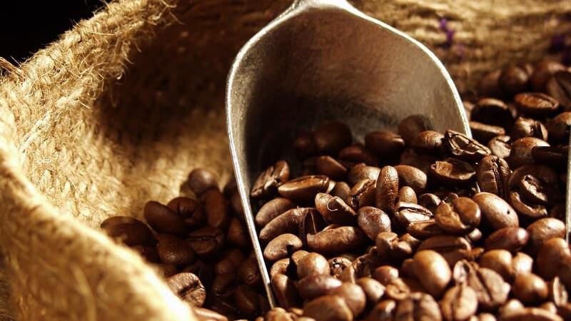 Ganze Kaffeebohnen im Sack mit kleiner Schaufel