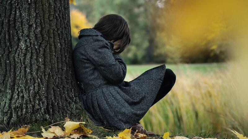 Herbstblues - Frau mit Winterdepression hockt traurig am Baumstamm auf Herbstwiese