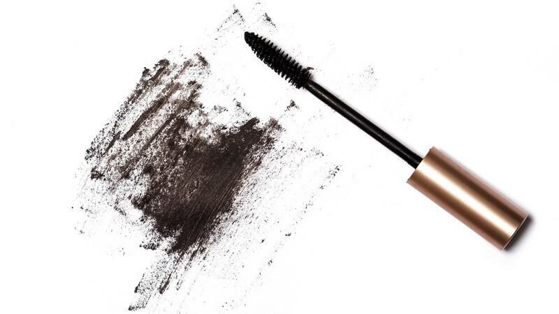 Mascara-Bürstchen und schwarze verwischte Schminke auf weißem Untergrund