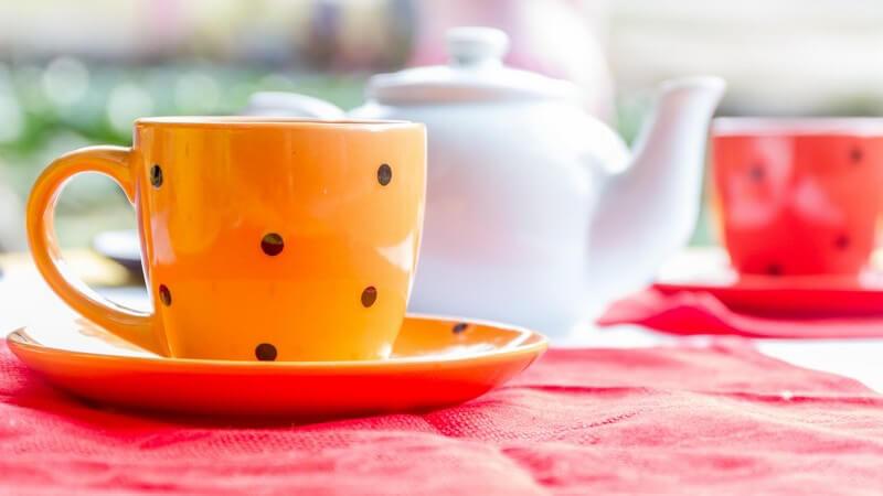 Orangene und rote Tasse mit Punkten neben weißer Teekanne auf Tisch im Cafe